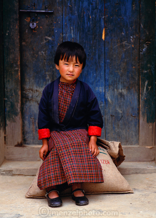 A young Bhutanese girl sits on a sack of rice in Gaselo, Bhutan. Published in Material World: A Global Family Portrait, page 6.