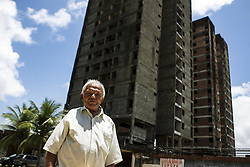 October 9, 2016 - Boa Viagem, Brazil - Mr. José in front of abandoned building and site trabvalho, in Recife, Brazil.  José Belmiro dos Santos is 84 years old, married to Rosalia Maria da Conceição and has nine children. He is retired since 1997 and works in a parking taking care of vehicles. The parking lot is situated in an abandoned building in Boa Viagem, in Recife, Pernambuco state, Brazil.Mr. José has to live in the building and can only visit family once a month. He thinks it's dangerous, because the parking lot is located inside a slum, but need to earn cash and stay home another person can take his job.Mr. José is part of a national statistic that indicates an increase in the number of pensioners who return to work in Brazil, 5.9% in the first quarter of 2012 to 6.5% in the second quarter 2016 (data from the Brazilian Institute of geography and Statistics), due to the current economic crisis.The government of the current President Michel Temer has as one of the goals the approval of Welfare Reform, thus ensuring clearer rules for retirement and the increase in the contribution to the public coffers. The approval of new rules for retirement might take the Brazil of the crisis and increase a government approval rating scored by polemics and an impeachment questioned by the opposition. (Credit Image: © Diego Herculano/NurPhoto via ZUMA Press)