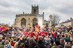 """© Licensed to London News Pictures. 05/01/2019. Haxey UK. Dale Smith """"the Fool"""" starts the Haxey Hood game today in the village of Haxey. The traditional game of Haxey Hood is taking place today in Haxey despite only one of the four pubs usually involved taking part. The Kings Arms, Duke William & The Loco pubs will all be closed today leaving just the Westwoodside's Carpenters Arms taking part. The traditional game, which dates from 1359, sees drinkers from pubs in the two villages attempt to win the Hood – a tube of leather – by 'swaying' it to their favoured watering hole in a muddy and bruising encounter which can take hours. Normally, victory is declared when the landlord of the winning pub takes delivery of the Hood on the pub doorstep but in the event of a Haxey win this year, a win will be claimed when the Hood reaches a pre-detemined point near the Kings Arms. Photo credit: Andrew McCaren/LNP"""