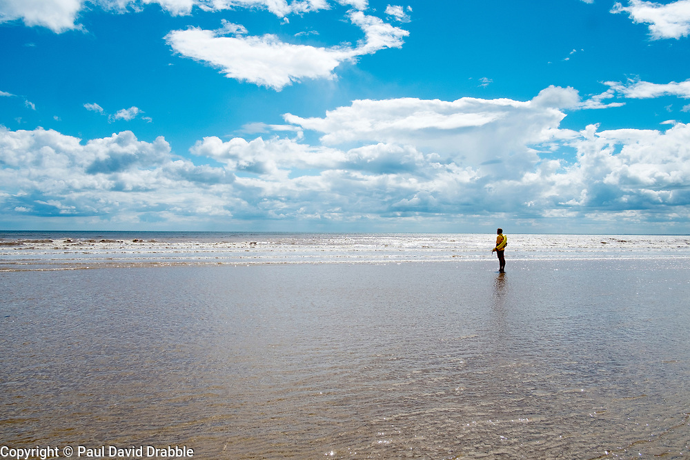 A Lifeguard of the Royal National Lifeboat Institution RNLI stands a lonely figure on Bridlington North Beach<br /> <br />  4 August 2016<br />  Copyright Paul David Drabble<br />  www.pauldaviddrabble.photoshelter.com