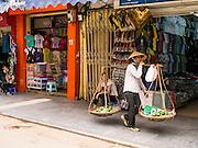02 APRIL 2012 - HANOI, VIETNAM: A woman selling fruit walks down a sidewalk in Hanoi, the capital of Vietnam.    PHOTO BY JACK KURTZ