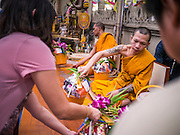 12 OCTOBER 2012 - RAI KHRING, NAKHON PATHOM, THAILAND:  People make offerings to the monks to make merit during a chanting service at Wat Rai Khring in Nakhon Pathom province. Wat Rai Khring was built in 1791. The Abbot at the time, Somdej Phra Phuttha Chan (Pook), named the temple after the district. When construction was completed, the Buddha image was brought from another temple and enshrined here. Later locals named the image ?Luang Pho Wat Rai Khing?. The Buddha image is of Chiang Saen style and is assumed to have been built by Lanna Thai and Lan Chang craftsmen.     PHOTO BY JACK KURTZ