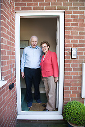 Older couple standing outside their front door together,