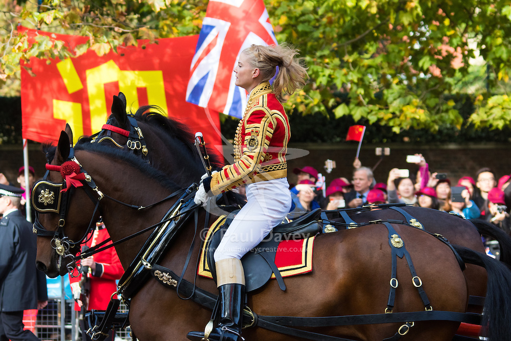 London, October 20th 2015. Following a Ceremonial welcoming to the UK by the Queen and The Duke of Edinburgh at Horse Guards Parade, a procession of carriages travels down the Mall past thousands of Chinese expatriates and Tibetan protesters. PICTURED: Her hat missing,  mounted soldier controls her rather excited horse.