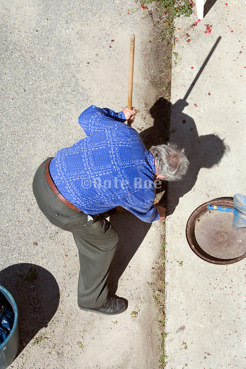 elderly person taking away the weeds in front of his house