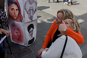 Two women mess about while having their portrait sketched by a street artist in Leicester Square. One woman clamps her hand over her friend's mouth as they sit for the artist who claims to make caricature portraits of the rich and famous including Michelle Obama (or is it Diana Ross?), Woody Allen and what appears to be Pakistani student Malala Yousafzai.
