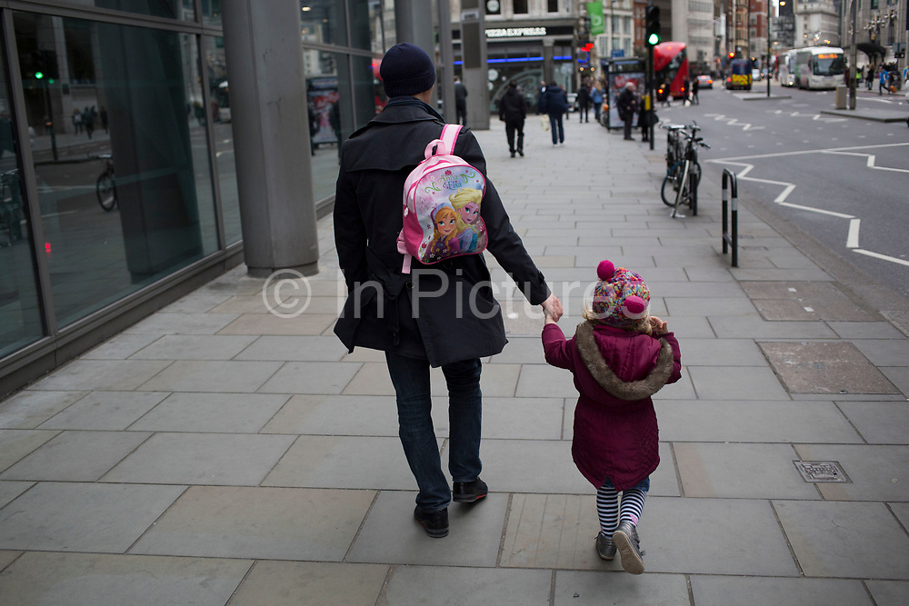Father carries his daughter's Anna and Elsa Frozen backpack. London, UK.