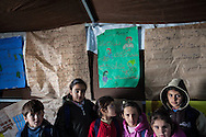 Syrian refugee children stand infront of a range of posters and instructions, in a school established in Islahiye camp, Turkey. 02/01/2013