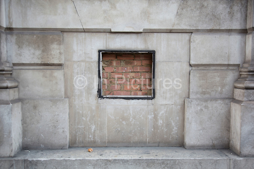 Square of brick wall behind the facade of a building, London, UK.