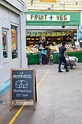 A shop sign promoting La Fauxmagerie, a plant-based cheesemonger, with a fruit and veg market stall in the background in Brixton Village on the 23rd May 2019 in London in the United Kingdom.