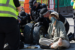 West Hyde, UK. 14th September, 2020. Officers from Hertfordshire Police's cutting team work to remove environmental activists from HS2 Rebellion using a lock-on arm tube to block a gate to the South Portal site for the HS2 high-speed rail link. Anti-HS2 activists blocked two gates to the site for the controversial £106bn rail link, one remaining closed for over six hours and another for over nineteen hours.