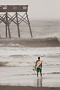 A lone surfer studies the surf churned up by passing Hurricane Irene on August 26, 2011 on Folly Beach, South Carolina. The Charleston area is expected to get only a mild brush with the category 3 hurricane as it heads up the coast.