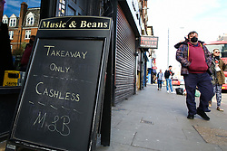 © Licensed to London News Pictures. 21/03/2020. London, UK. A man wearing a face mask walks past a 'TAKEAWAY ONLY' sign outside a closed restaurant in Green Lanes, Haringey, north London. The closures follow Prime Minister, BORIS JOHNSON'S request that all restaurants, cafes and pubs should close until further notice as the Coronavirus impact worsens. Photo credit: Dinendra Haria/LNP