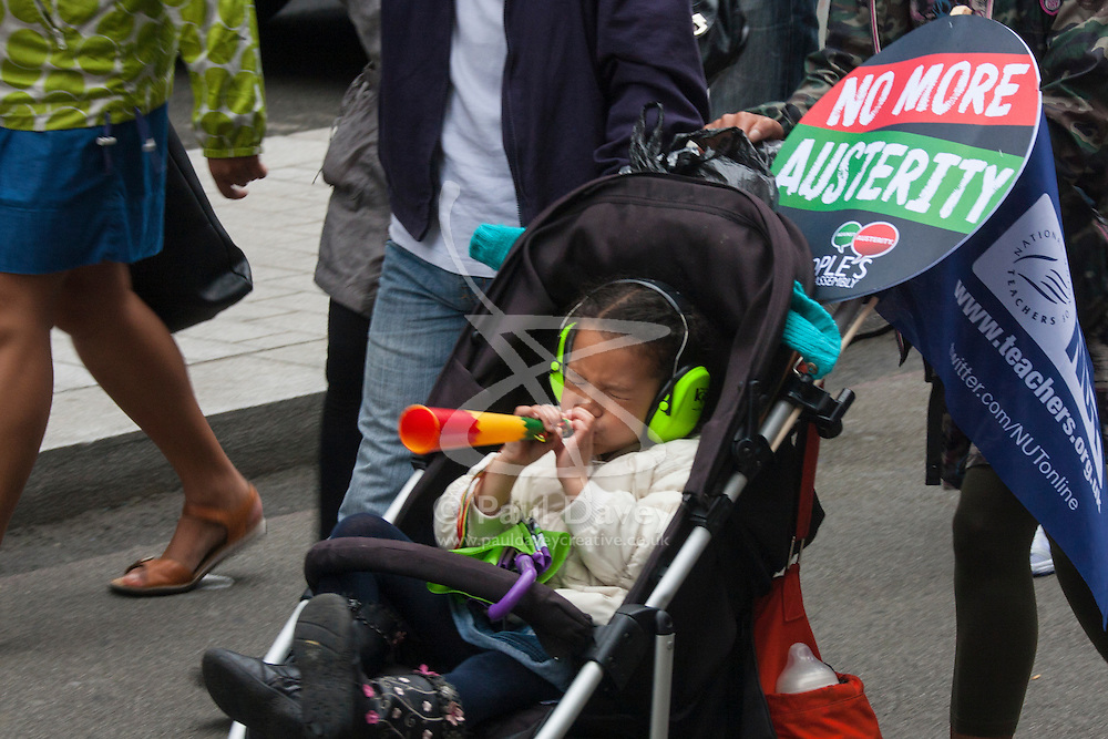 London, July 10th 2014. A toddler blows a horn as thousands of striking teachers, government workers and firefighters march  through London in protest against cuts and working conditions.