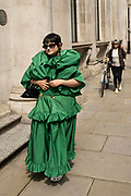 Young woman wearing an unusual green dress and white Crocs walks along Old Broad Street in the City of London on 26th May 2021 in London, United Kingdom. As the coronavirus lockdown continues its process of easing restrictions, the City remains far quieter than usual, which asks the question if normal numbers of people and city workers will ever return to the Square Mile.