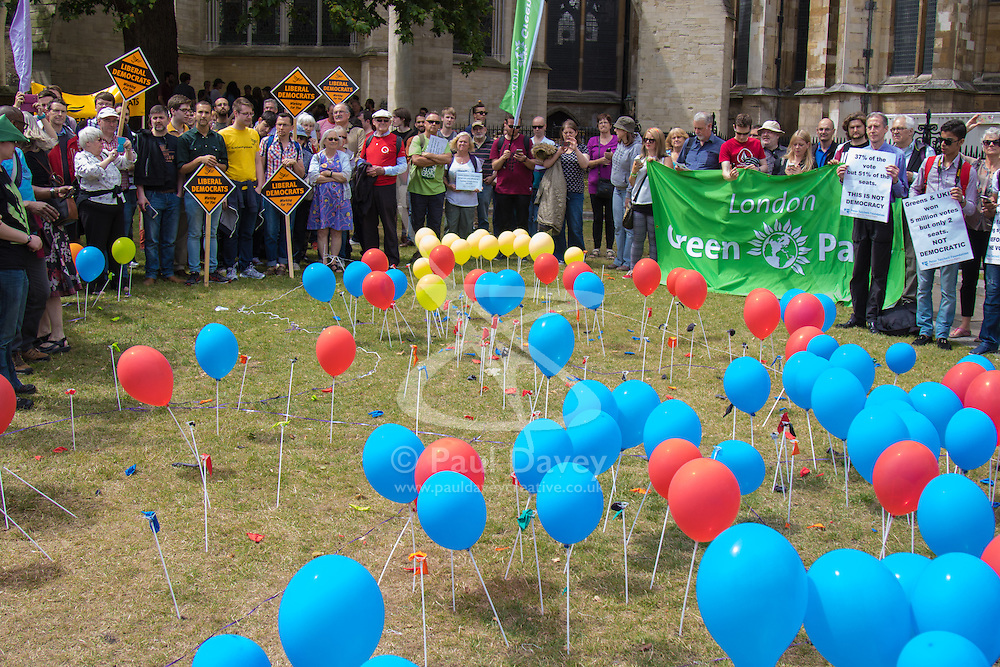 """Old Palace Yard, Westminster, July 25th 2015. Protesters gather outside the Houses of Parliament to demand electoral reform, including proportional representation rather than the first-past-the-post method that saw the Tories gain a majority. PICTURED: Popped ballons representing """"unrepresented"""" votes stand amongst those still inflated representing parties that succeeded through thye first-past-the-post system."""