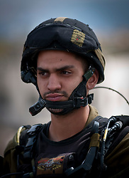 © London News Pictures. 14/03/2011. An Israeli soldier monitors a demonstration against continued settlement building around Bethlehem in the occupied West Bank of Palestine. 13/03/11