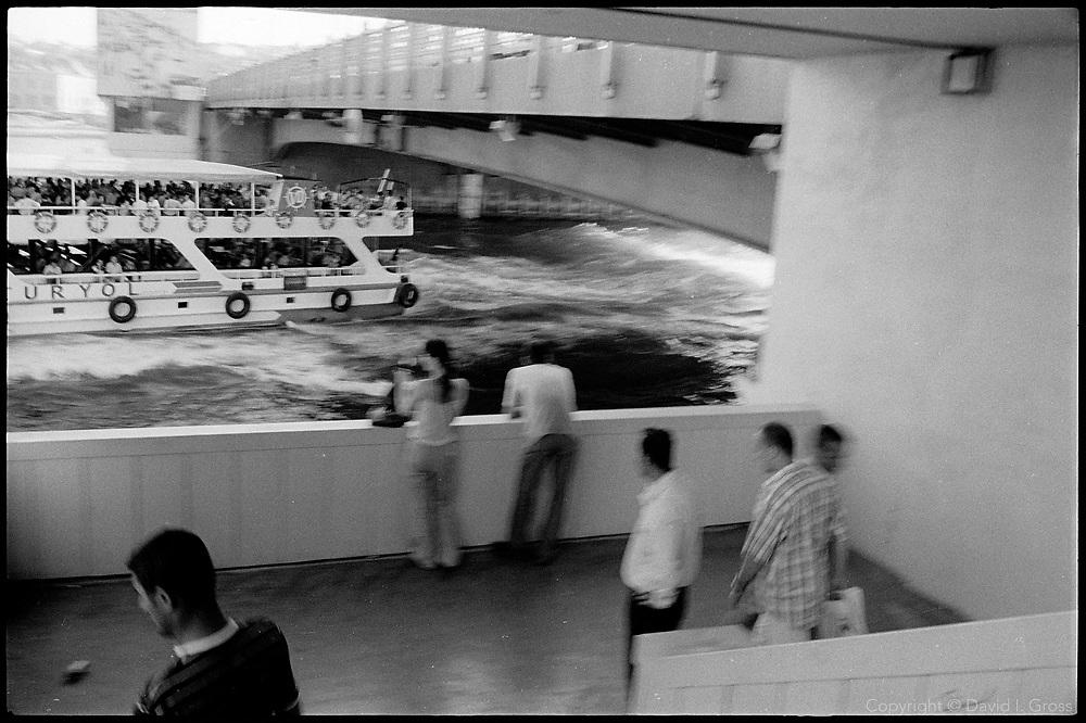 A ferryboat passes under the Galata Bridge in Istanbul, Turkey.