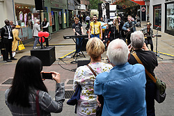 """© Licensed to London News Pictures. 05/09/2018. LONDON, UK. Queen tribute band """"Bulsara and the Queenies"""" perform for fans of Freddie Mercury and members of the public in Carnaby Street who don moustaches during """"Freddie for a Day"""", a fundraising event in aid of the Mercury Phoenix Trust on Freddie Mercury's birthday. Photo credit: Stephen Chung/LNP"""