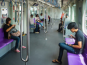 "23 AUGUST 2016 - NONTHABURI, NONTHABURI, THAILAND: Passengers in a nearly empty train car on the ""Purple Line,"" the new Bangkok commuter rail line that runs from Bang Sue, in Bangkok, to Nonthaburi, a large Bangkok suburb. The Purple Line is run by the  Metropolitan Rapid Transit (MRT) which operates Bangkok's subway system. The Purple Line is the fifth light rail mass transit line in Bangkok and is 23 kilometers long. The Purple Line opened on August 6 and so far ridership is below expectations. Only about 20,000 people a day are using the line; officials had estimated as many 70,000 people per day would use the line. The Purple Line was supposed to connect to the MRT's Blue Line, which goes into central Bangkok, but the line was opened before the connection was completed so commuters have to take a shuttle bus or taxi to the Blue Line station. The Thai government has ordered transit officials to come up with plans to increase ridership. Officials are looking at lowering fares and / or improving the connections between the two light rail lines.     PHOTO BY JACK KURTZ"