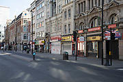 Closed down shops on Oxford Street, Londons main shopping and retail area normally full of thousands of shoppers and traffic is virtually deserted due to the Coronavirus outbreak on 23rd March 2020 in London, England, United Kingdom. Following government advice most shoppers are staying at home leaving the streets quiet, empty and eerie. Coronavirus or Covid-19 is a new respiratory illness that has not previously been seen in humans. While much or Europe has been placed into lockdown, the UK government has announced more stringent rules as part of their long term strategy, and in particular social distancing.