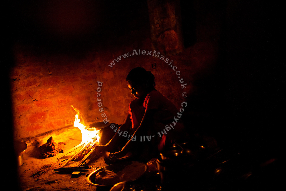 Arti, 16, Poonam's eldest sister, is cooking some chapattis, the typical flat India bread, while sitting next to the fireplace inside her family's newly built home in Oriya Basti, one of the water-affected colonies in Bhopal, Madhya Pradesh, India, near the abandoned Union Carbide (now DOW Chemical) industrial complex.