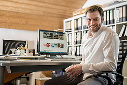 Portrait of a mid adult businessman drinking coffee in an office and smiling, Bavaria, Germany