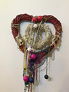 Hanging double Hearts- Big red one on outside smaller white one on inside. Made of plastic straw like material. In Souls Grown Deep Book by William Arnett- 19 in wide- 9x9 smaller heart. Adorned with bobbers and mardi gras beads<br />