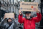Paid to Pollute claimants Kairin van Sweeden and Jeremy Cox outside Downing Street on 2nd October 2021 in London, United Kingdom. Kairin and Jeremy are two of the three climate activists taking the UK government to court over the billions of pounds of public money it spends supporting the oil and gas industry, as part of the Paid to Pollute campaign. <br /> <br /> Jeremy Cox is a retired former oil worker, current Extinction Rebellion activist, beekeeper, green woodworker and amateur baker.<br /> <br /> Kairin van Sweeden is an SNP Common Weal organiser for the North east of Scotland, the daughter of an oil worker, an Aberdeen quine and Executive Director of the Modern Money Scotland think tank.