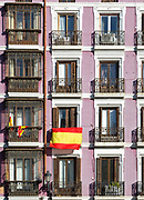 Geometric pattern of historic apartments with national flag, Calle de Bailen, Madrid city centre, Spain