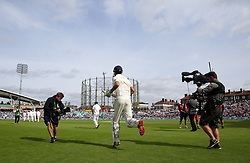 England's Alastair Cook runs out onto the field to a standing ovation as he continues his final test innings during the test match at The Kia Oval, London.