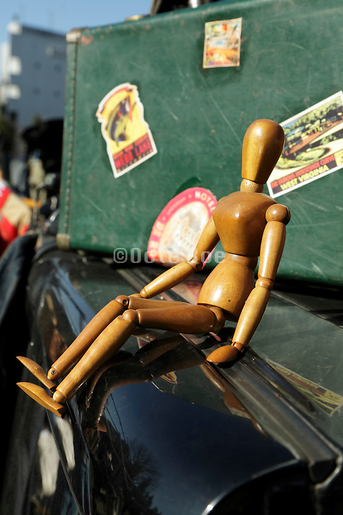 figurine sitting on the hood of an old car with a travel suitcase in the background