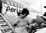 A young Vietnamese woman and her child being assisted from the aircraft by an Aer Lingus hostess. As part of a UNHCR initiative, Ireland agreed to take some of the  Vietnamese (boat people) refugees. A temporary refugee centre was set up in the grounds of Blanchardstown Hospital to accommodate the families, from where they were assimilated into the community. Refugees Arriving<br />
