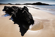 Barnicle and mussel covered rock surrounded by a clear sea water pool, in pristine sand at Llanddwyn Island, West Anglesey, Wales