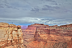A visitor takes in the view of Shafter Canyon Overlook on a beautiful stormy evening in Canyonlands National Park of Moab Utah