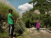 Boy and girl play at spraying water at eachother with a hose. <br /> Around Kamaris village, upper Hunza.