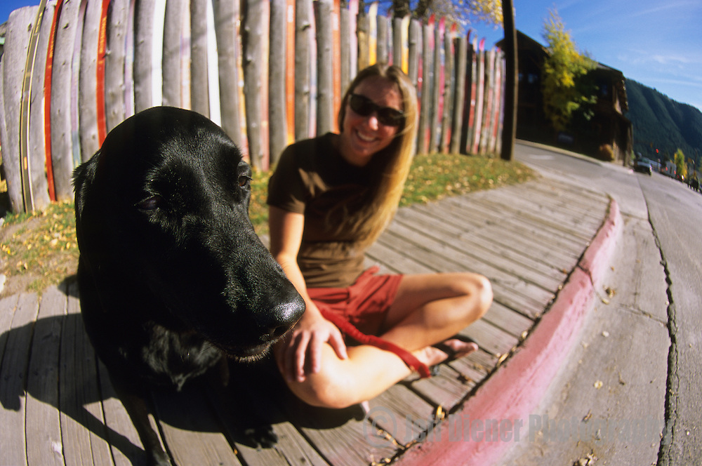 A young woman sits with her dog in the town of Jackson, Wyoming.