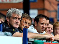 Manchester City manager Mark Hughes sits impassively in the stands.<br />