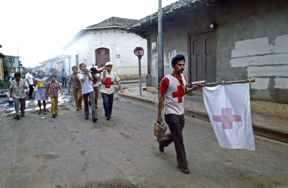 Nicaraguan Cruz Roja (Red Cross) workers carry the wounded and escort noncombatants out of the besieged city of Leon during a break in street fighting in the 1978 Civil War in Nicaragua.