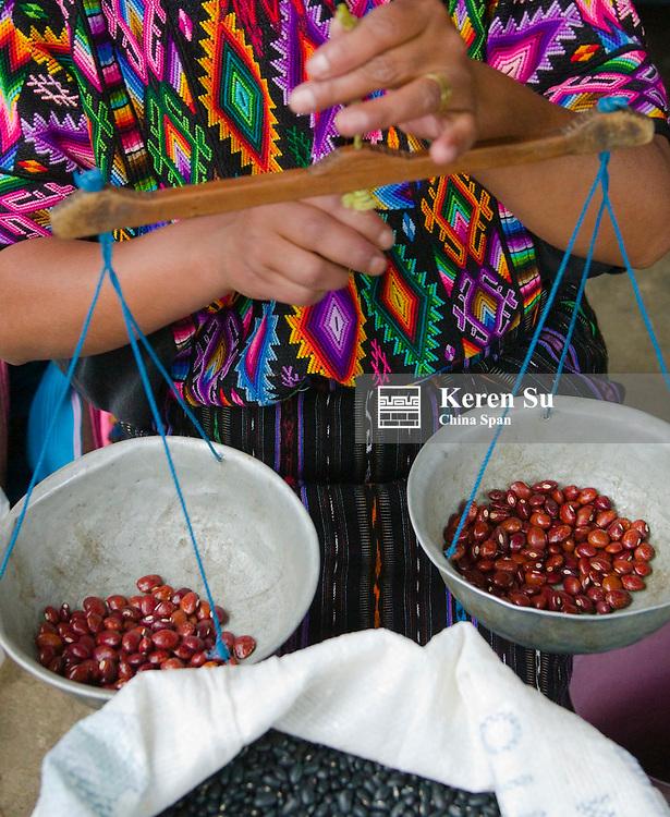 Woman weighing beans at the market, Chichicastenango, Guatemala