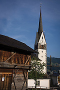 Typical Dolomites church architecture and timber barn in Leonhard-St Leonardo, a Dolomites village in south Tyrol, Italy.