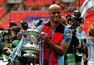 Vincent Kompany (4) of Manchester City holds up the FA Cup at full time  during the The FA Cup Final match between Manchester City and Watford at Wembley Stadium, London, England on 18 May 2019.