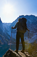 A woman wearing a backpack and holding treking poles standing above a lake looking up toward the mountains, Washington Cascades, USA.