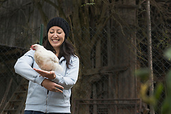 Farmer woman with white chicken bird and smiling in farm, Bavaria, Germany