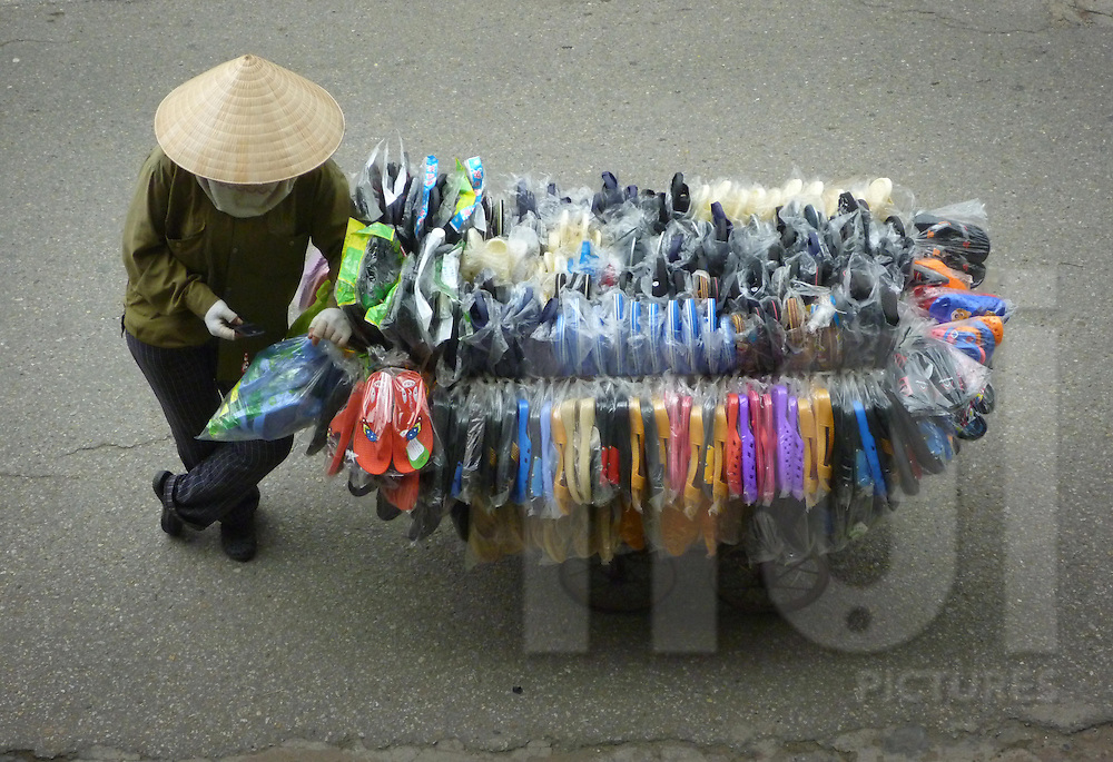 A shoe and flip-flop seller wearing a conical hat leans to her cart and sends a text message on her mobile phone in Hanoi, Vietnam