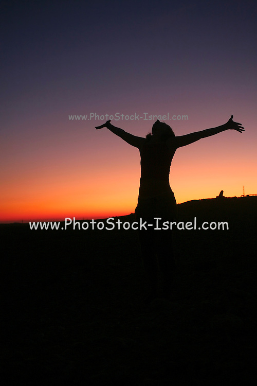 Silhouette of an exited woman at sunset