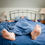 A man sleeps in bed with his feet hanging out. Missoula Photographer