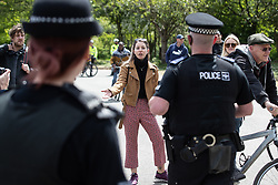 """© Licensed to London News Pictures. 16/05/2020. Manchester, UK. A woman shouts abusive comments about Jimmy Saville , Jeffrey Epstein , Aldus Huxley and George Orwell at police , at the demo . An anti-lockdown, """"mass gathering"""" demonstration is held in Platt Fields Park in protest at government measures to control the spread of Covid-19. A group calling itself the UK Freedom Movement has organised a series of demonstrations across the UK. Photo credit: Joel Goodman/LNP"""