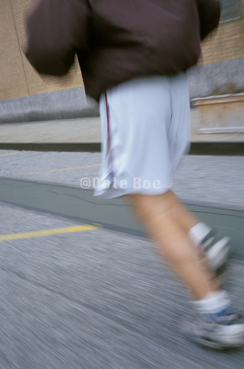 view from behind of a person jogging on street