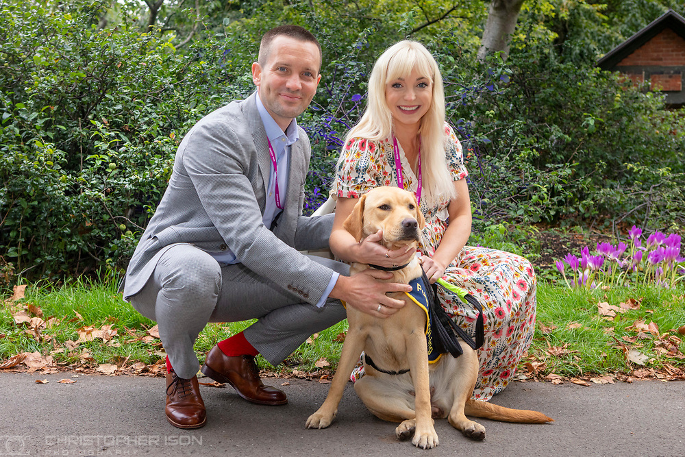 ***Editorial free to use image***<br /> Actors Jack Ashton and Helen George with female guide dog puppy in training, Flash, at the Chelsea Flower Show. Flash is an eight-month-old Labrador named for Guide Dogs's 90th anniversary. <br /> Guide Dogs have an Artisan Garden at RHS Chelsea this year in celebration of 90 years of guide dog partnerships in Britain.<br /> Picture date: Monday September 20, 2021.<br /> Photograph by Christopher Ison ©<br /> 07544044177<br /> chris@christopherison.com<br /> www.christopherison.com